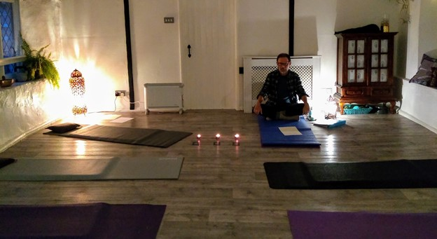Man sat on yoga mat in studio with candles around